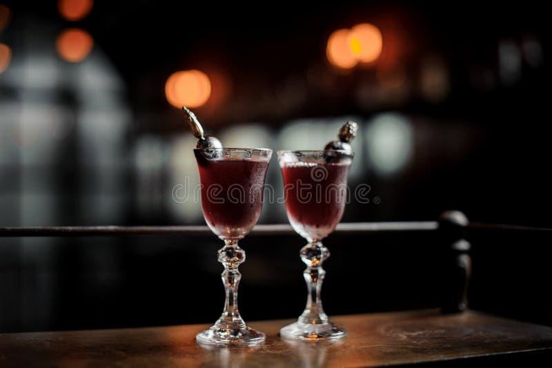 Två eleganta exponeringsglas fyllde med den nya sötsaken och den starka sommarArnaud coctailen på den mörka suddiga bakgrunden av royaltyfria foton