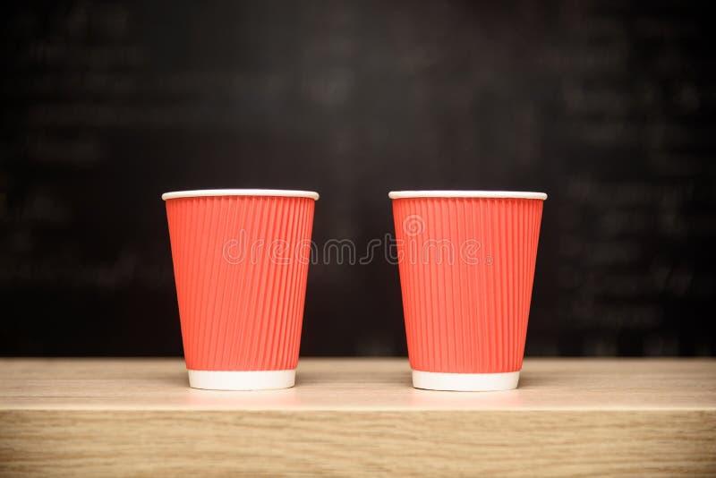 Två engångs- pappers- koppar för kaffe, trästångräknare, mörk mjuk bakgrund med att markera mitten och kopia gör mellanslag, plan royaltyfria bilder