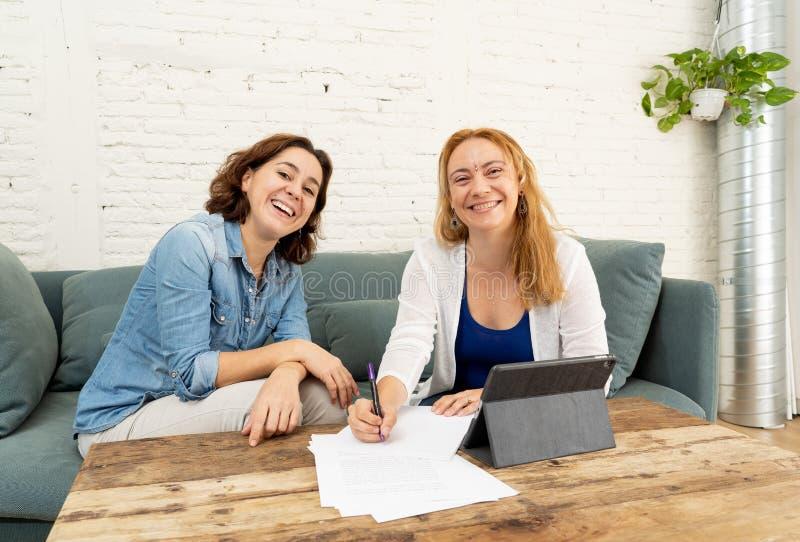 Två entreprenörkvinnor som tillsammans arbetar på design på minnestavlan för deras online-affär arkivbilder