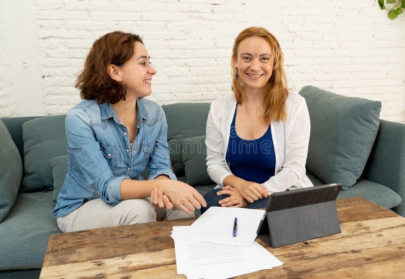 Två entreprenörkvinnor som tillsammans arbetar på design på minnestavlan för deras online-affär royaltyfri bild