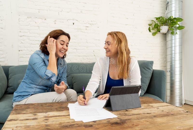 Två entreprenörkvinnor som tillsammans arbetar på design på minnestavlan för deras online-affär royaltyfri fotografi