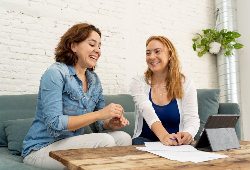 Två entreprenörkvinnor som tillsammans arbetar på design på minnestavlan för deras online-affär fotografering för bildbyråer