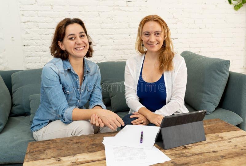 Två entreprenörkvinnor som tillsammans arbetar på design på minnestavlan för deras online-affär arkivfoton