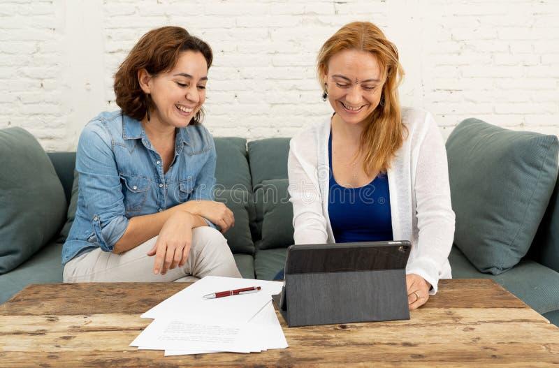 Två entreprenörkvinnor som tillsammans arbetar på design på minnestavlan för deras online-affär arkivbild