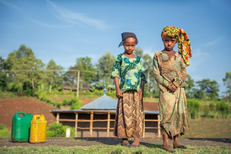 Två ethiopian flickor som går för vatten nära Addis Ababa, Etiopien royaltyfria bilder
