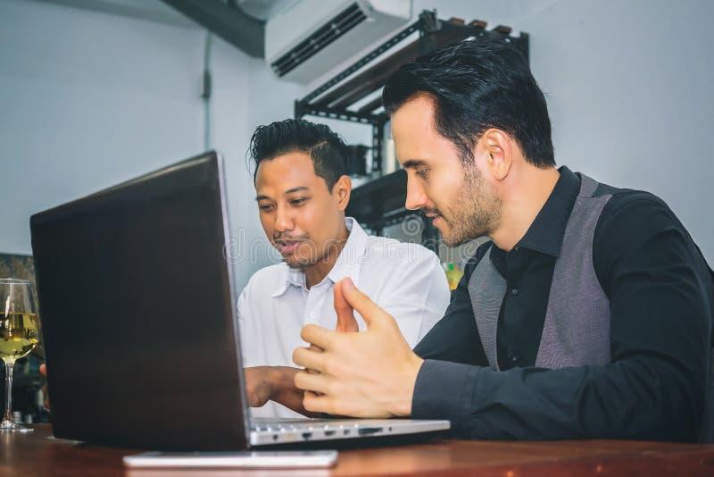 Två etniska affärspersoner diskuterar arbete för ömsesidiga succes arkivbilder