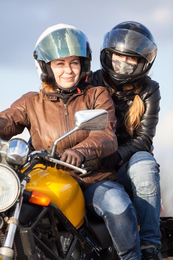 Två europeiska kvinnor som tillsammans kör på en cykel, passageraresammanträde bak chauffören arkivfoton