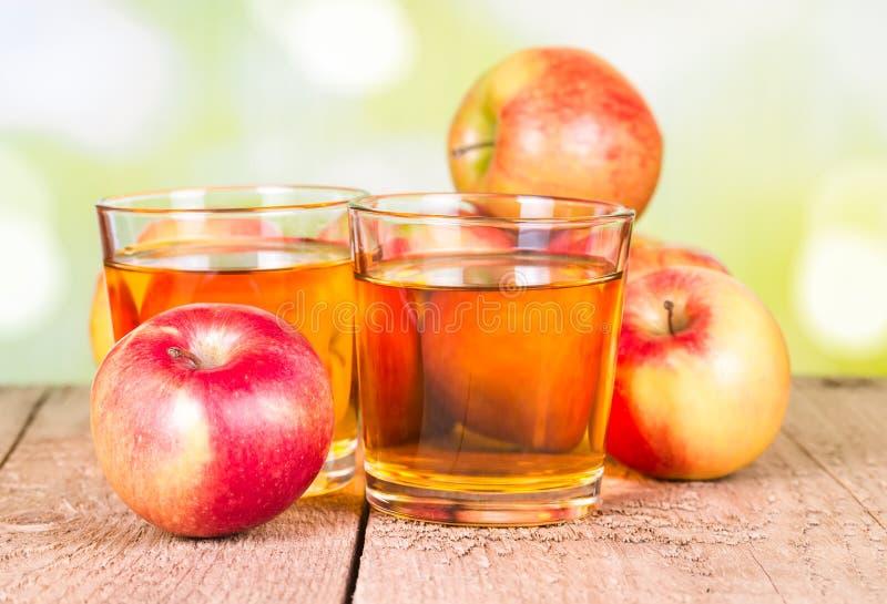Två exponeringsglas av äppelmust arkivbild