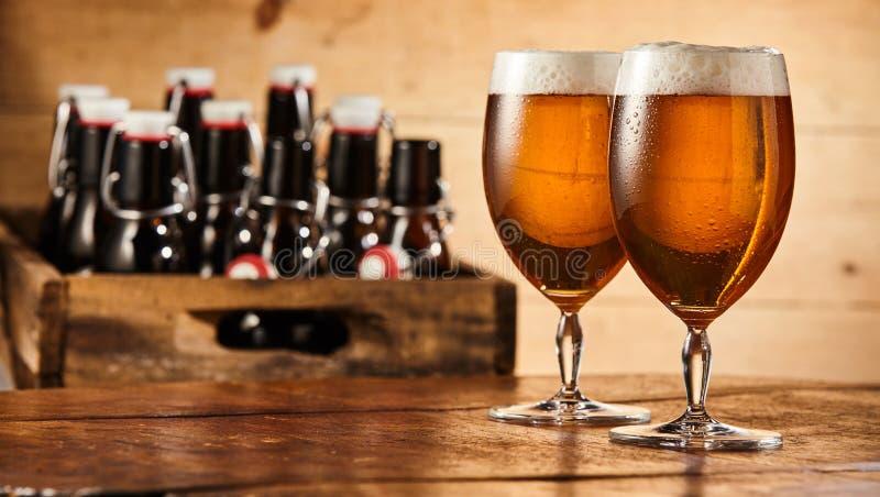 Två exponeringsglas av öl på en stångräknare arkivbilder