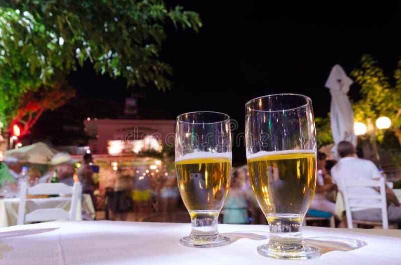Två exponeringsglas av öl på en tabell royaltyfri bild