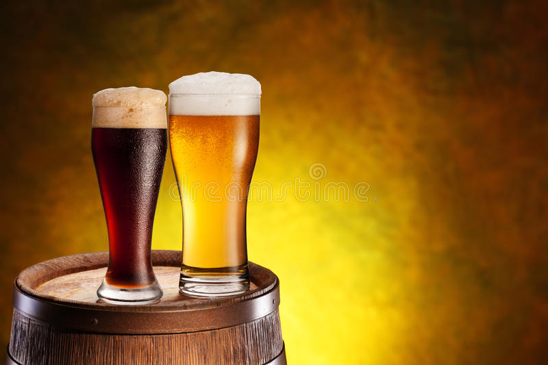 Två exponeringsglas av öl på en trätrumma. royaltyfri bild