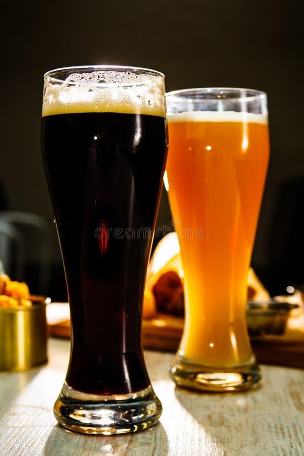 Två exponeringsglas av ölanseende på tabellen på en mörk bakgrund arkivbilder
