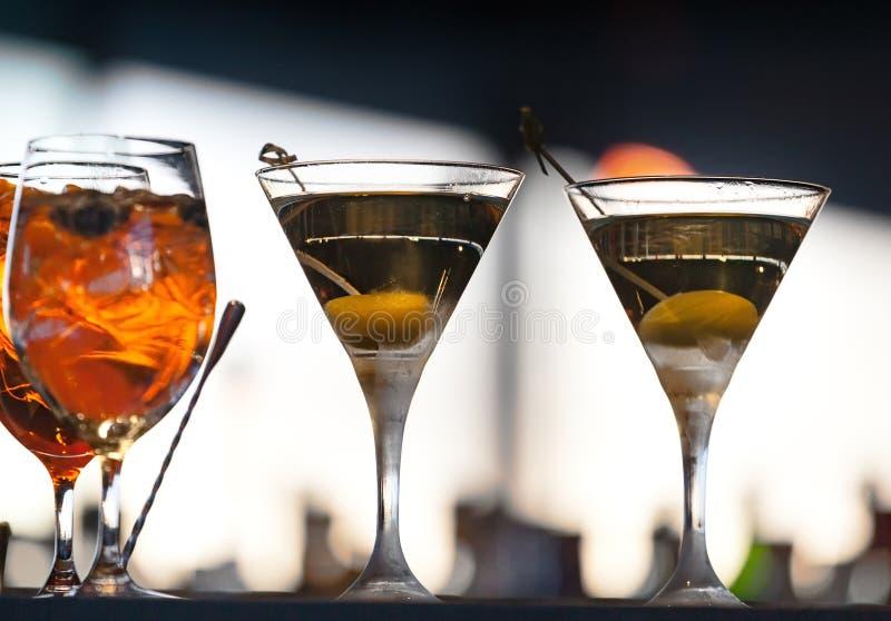 Två exponeringsglas av alkoholdrycker med oliv fotografering för bildbyråer