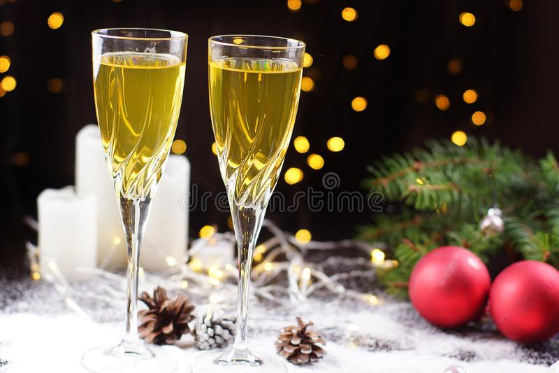 Två exponeringsglas av champagne eller fruktsaft på tabellen som dekoreras med en glödande girland, röda bollar, en julgranfilial arkivbilder
