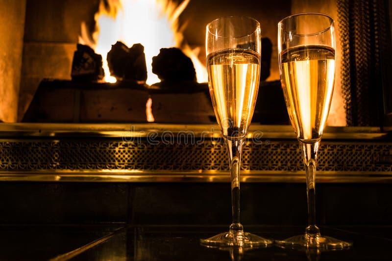 Två exponeringsglas av champagne framme av en romantisk brand arkivfoto