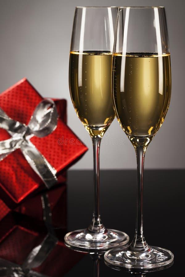Två exponeringsglas av champagne med en present i backgro arkivbild