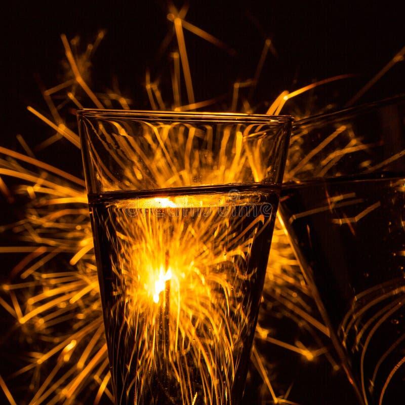 Två exponeringsglas av champagne med fyrverkeritomtebloss arkivfoton