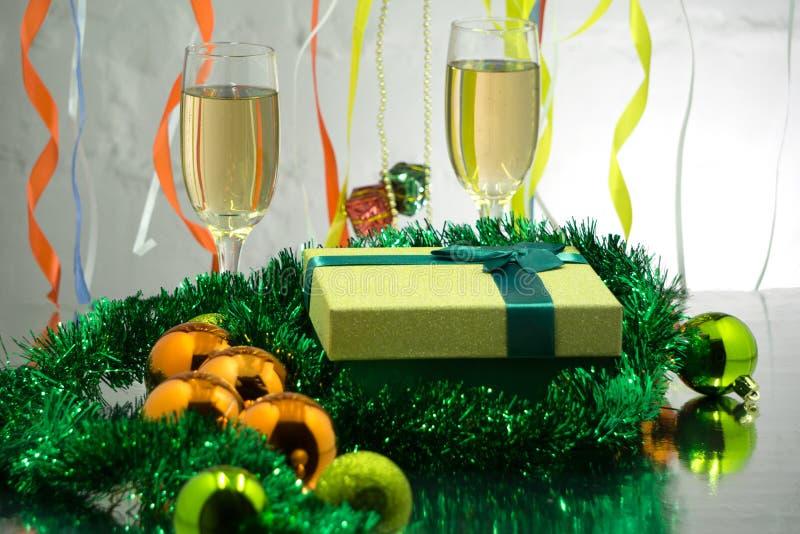 Två exponeringsglas av champagne med garneringar för ` ett s för nytt år för pepparkakahus på en tabell för ` s för nytt år på en royaltyfria foton