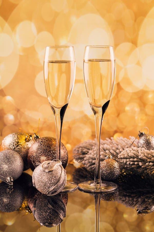 Två exponeringsglas av champagne med guld- ljus bokeh på bakgrund arkivbilder
