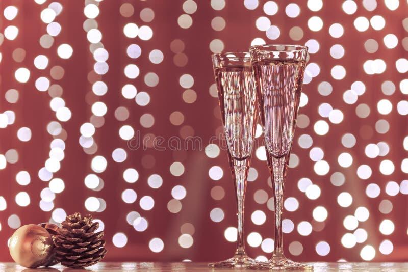 Två exponeringsglas av champagne med julleksaker Festlig ljusbok royaltyfri bild