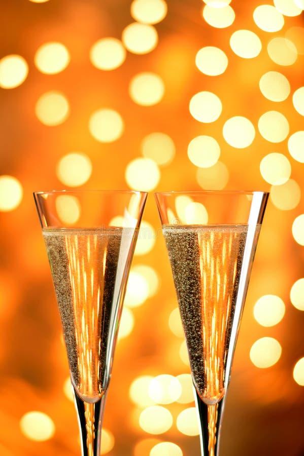 Två exponeringsglas av champagne mot bokehbakgrund. royaltyfri bild