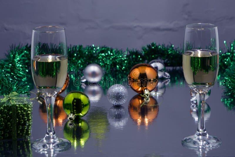 Två exponeringsglas av champagne som är klara för julberöm, på purpurfärgad bakgrund arkivfoto