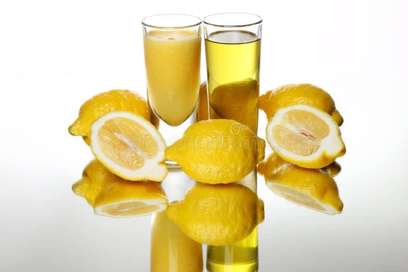 Två exponeringsglas av citronjuice och smoothies near nya citroner royaltyfri foto