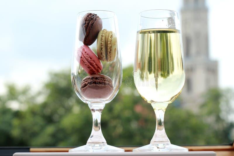 Två exponeringsglas av franska macarons och vitt vin arkivfoton