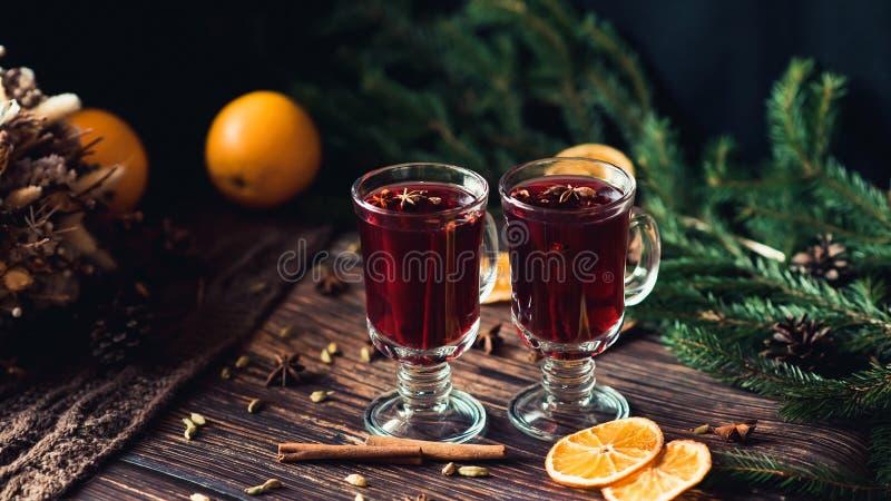 Två exponeringsglas av funderat vin med kryddor och orange skivor på en trätabell Varm alkoholdryck arkivbilder