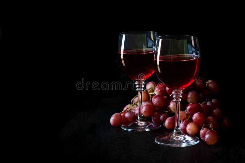 Två exponeringsglas av hemlagat rosa vin och druvor royaltyfria foton