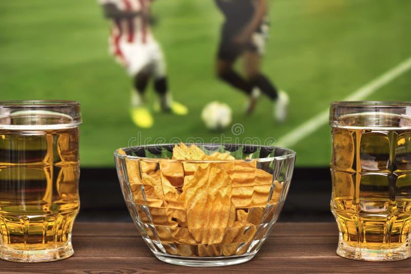 Två exponeringsglas av kallt öl och chiper, fotbollsmatch i bakgrund royaltyfria bilder