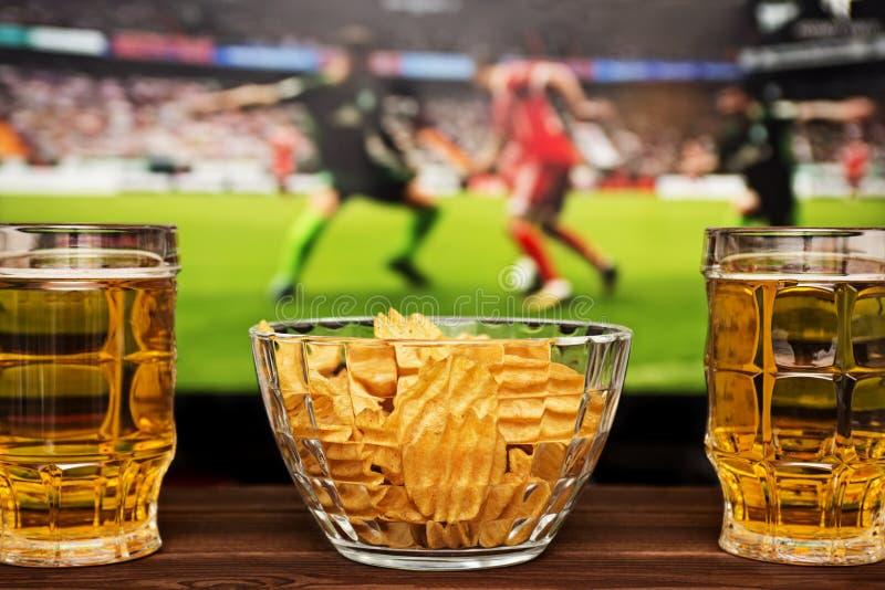 Två exponeringsglas av kallt öl och chiper, fotbollsmatch i bakgrund royaltyfri foto