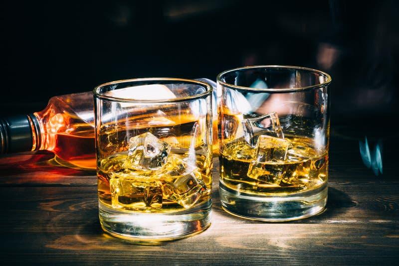 Två exponeringsglas av kväv whisky eller konjak med iskuber och flaskan av alkoholstarksprit på mörk träbakgrund royaltyfria foton