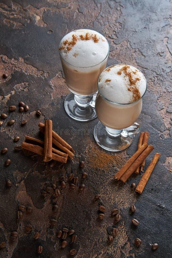 Två exponeringsglas av latte på en trätabell med kaffebönor och kanel royaltyfri bild