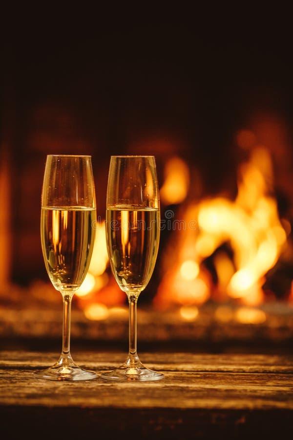 Två exponeringsglas av mousserande champagne framme av den varma spisen C royaltyfri fotografi