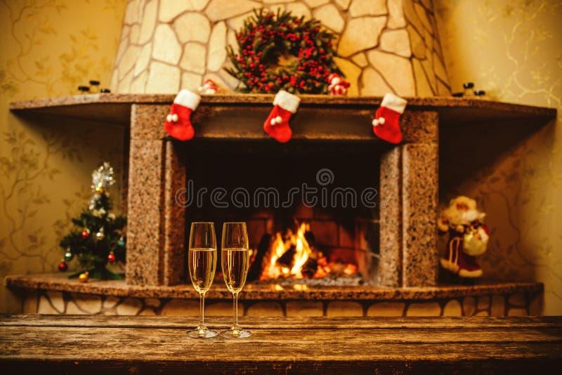 Två exponeringsglas av mousserande champagne framme av den varma spisen C arkivfoto
