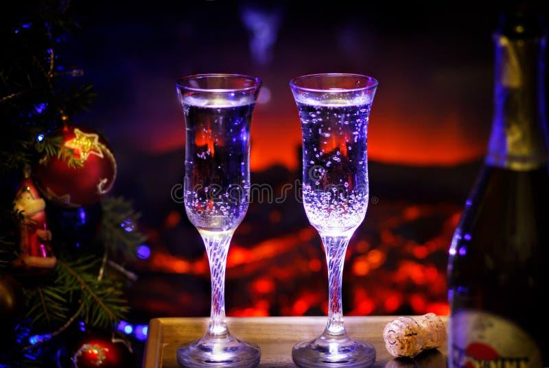 Två exponeringsglas av mousserande champagne framme av den varma spisen Slags tvåsittssoffa kopplade av magisk atmosfär i ett cha fotografering för bildbyråer