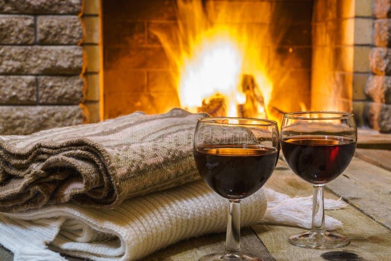 Två exponeringsglas av rött vin och den woolen saker near den hemtrevliga spisen royaltyfria bilder