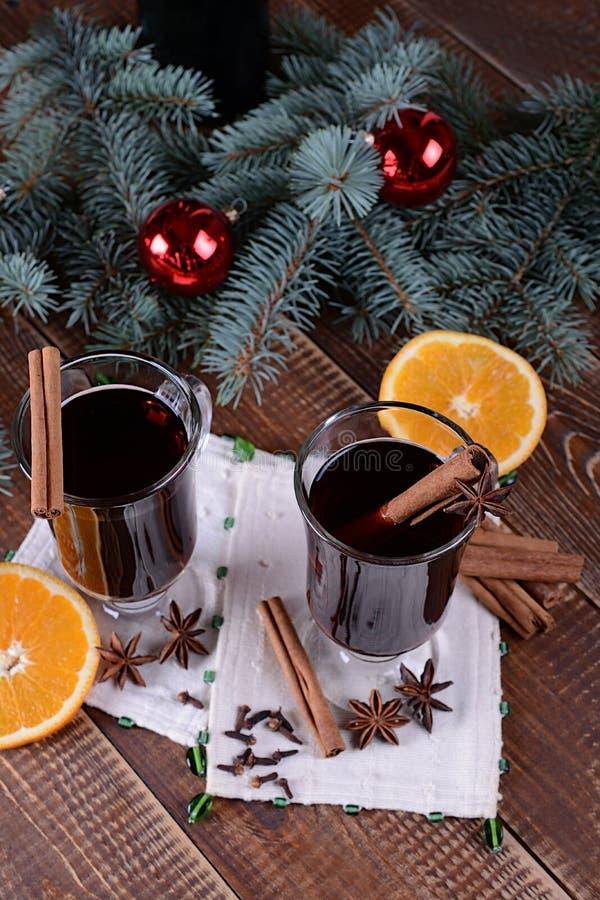 Två exponeringsglas av varmt funderat vin på en bakgrund av traditionellt julpynt arkivbilder