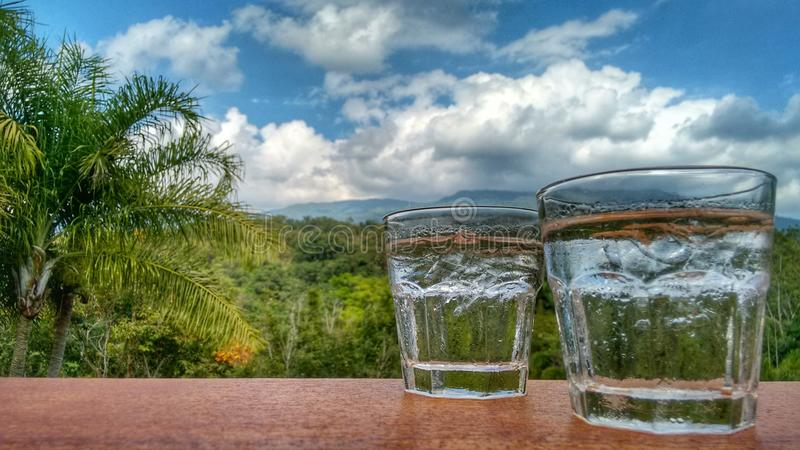 Två exponeringsglas av vatten framme av den rena naturen arkivbilder