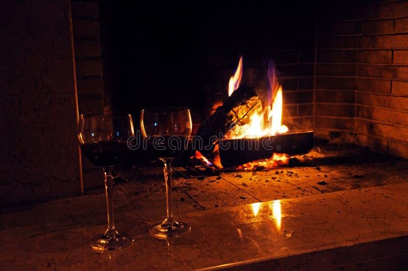 Två exponeringsglas av vin nära spisen arkivfoto