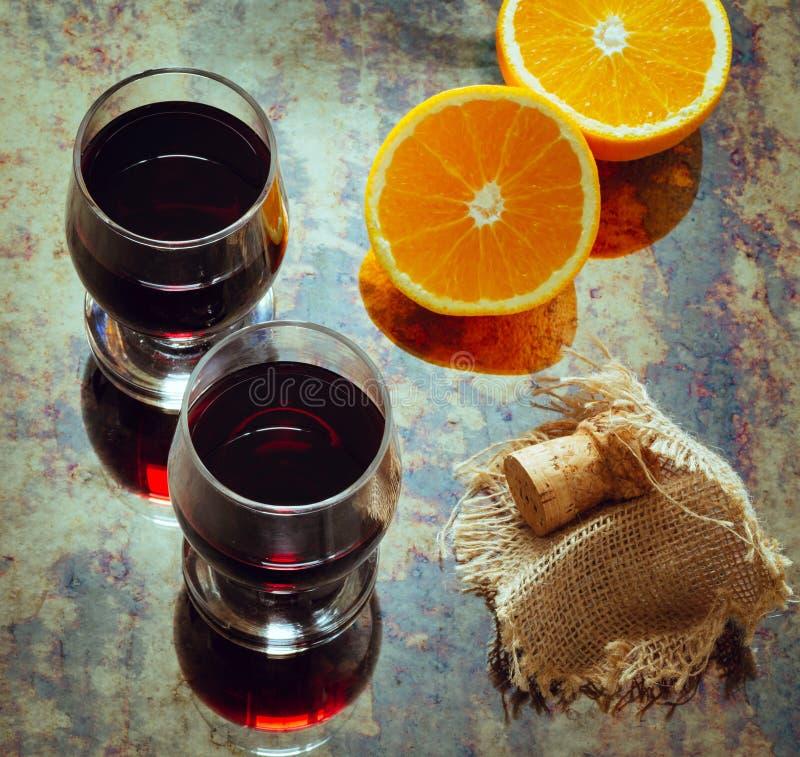Två exponeringsglas av vin och stycken av apelsinen, foto i tappningstil arkivbilder