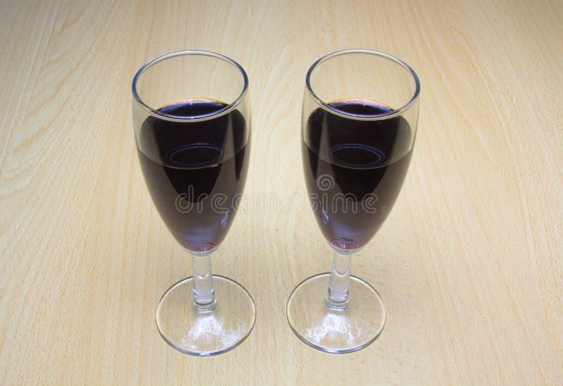 Två exponeringsglas av vin på en träbakgrund arkivfoto