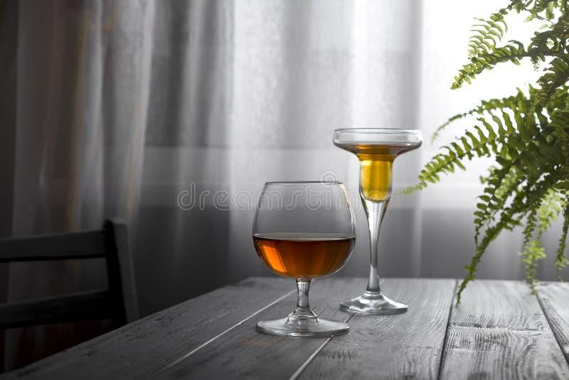 Två exponeringsglas av vin som förläggas på en trätabell på bakgrunden av ett fönster med en vit gardin Naturligt ljus från a arkivfoto