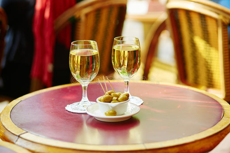 Två exponeringsglas av vitt vin och oliv arkivbilder