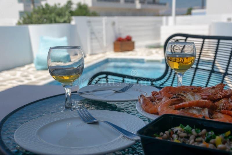 Två exponeringsglas av vitt vin och räkor på tabellen vid pölen royaltyfri foto