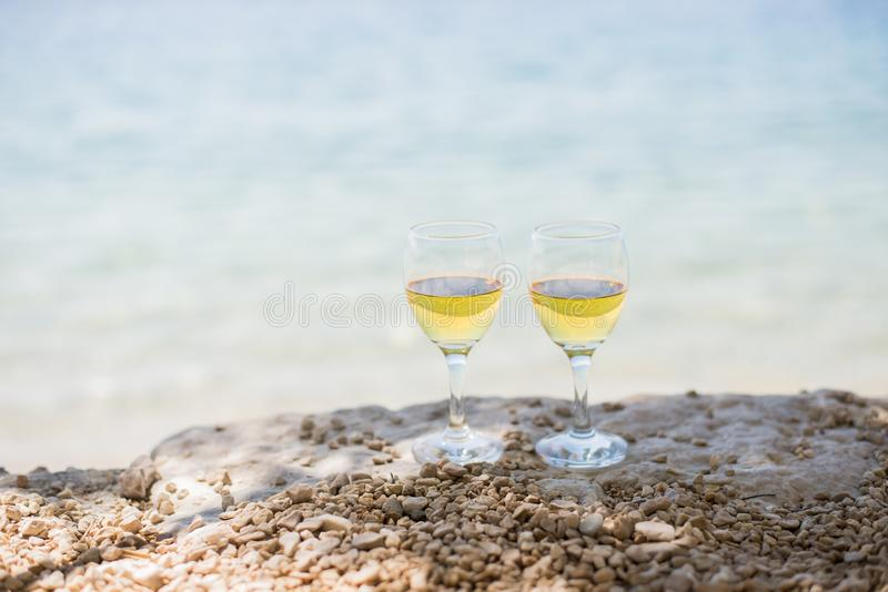 Två exponeringsglas av vitt vin på stranden med havet på bakgrund royaltyfria bilder