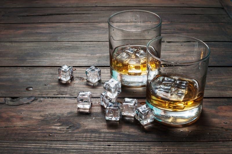 Två exponeringsglas av whisky med iskuber tjänade som på träplankor Tappningcountertop och ett exponeringsglas av hård starksprit royaltyfri fotografi