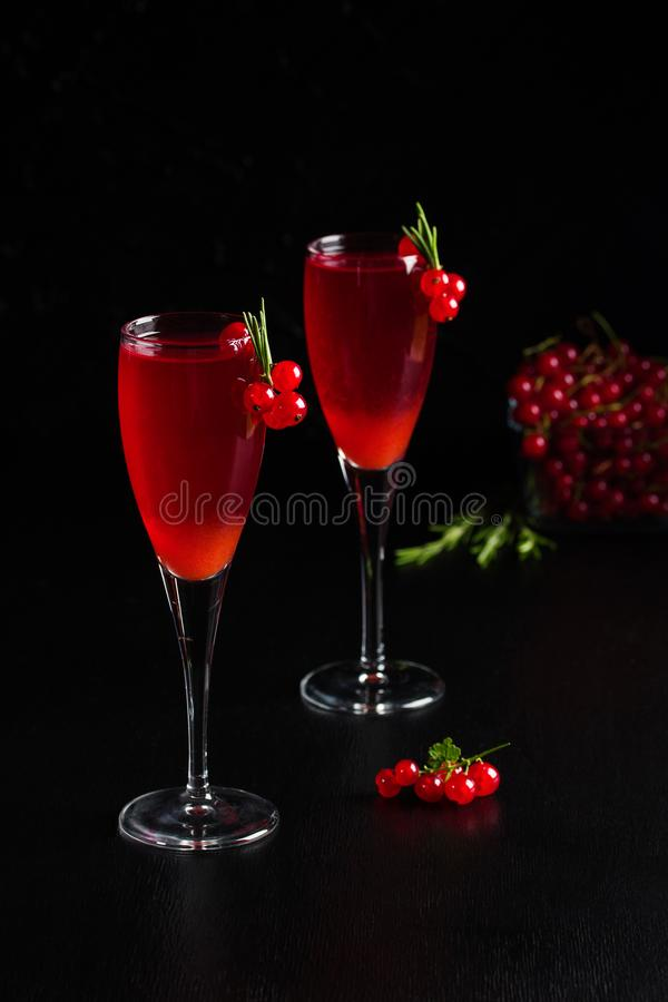 Två exponeringsglas fruktsaft för redcurrantvindrink dekorerade med rosmarin royaltyfri bild