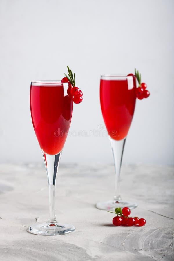 Två exponeringsglas fruktsaft för redcurrantvindrink dekorerade med rosmarin royaltyfria bilder